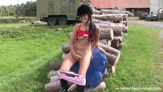 Horny teenage girl Lucy does it on a log pile with dildo