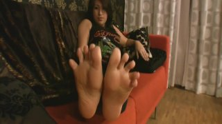 Girl on sofa points toes